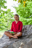 Smiling 20s girl reading a summer book under a tree. Outdoors reading - beautiful young suntanned blond woman sitting on a giant stone in the shade staring at Royalty Free Stock Images