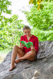 Smiling 20s girl reading a summer book under a tree. Outdoors reading - thrilled young suntanned blond woman reading a book on a giant stone in the shade for Royalty Free Stock Photos