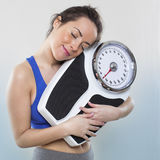 Smiling 20s girl taking care of her kilos or pounds with her wellness best friend. Sports and wellness concept - satisfied young woman in love with her weight royalty free stock image
