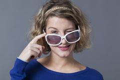 Smiling 20s girl winking over her lady sunglasses Stock Images