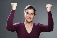 Smiling 30s woman glowing from within with hands up Stock Image