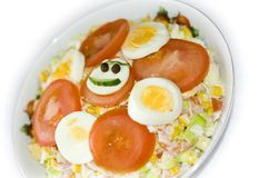 Smiling salad with ham. Healthy salad with smile decorated with cucumber, egg, toamto and black pepper Stock Photo