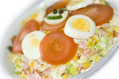 Smiling salad with ham. Healthy salad with smile decorated with cucumber, egg, toamto and black pepper Stock Images