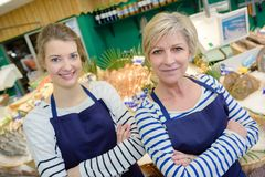 Smiling sales assistants working at counter in fish store. Fish royalty free stock photography