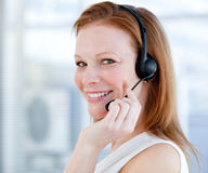 Smiling sales representative woman with earpiece. Sitting in a modern building Stock Image
