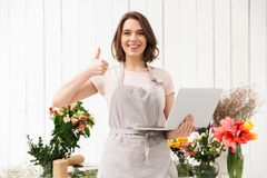 Smiling sales woman standing near bouquets in flower shop, and s. Smiling sales woman standing near bouquets in flower shop and showing thumb up with laptop in Stock Image
