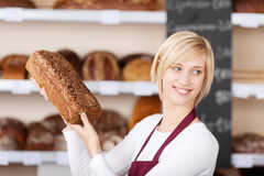 Smiling salesgirl holding bread Stock Photos