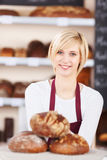 Smiling salesgirl working in bakery Royalty Free Stock Photography