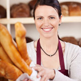 Smiling saleslady in a bakery. Holding a large white paper packet of freshly baked crusty baguettes in her arms Royalty Free Stock Images
