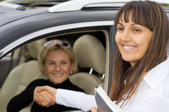Smiling saleslady congratulating the new owner Stock Image