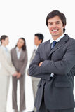 Smiling salesman with arms crossed and team behind him Royalty Free Stock Photos