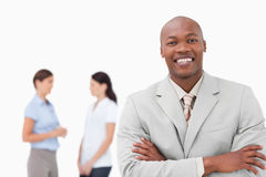 Smiling salesman with arms folded and associates behind him Royalty Free Stock Images