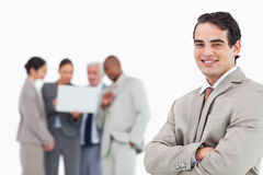 Smiling salesman with arms folded and colleagues behind him Stock Photo