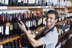Smiling Salesman Arranging Wine Bottle On Shelf. Portrait of smiling salesman arranging wine bottle on shelf in shop stock photography