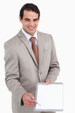 Smiling salesman asking for signature. Against a white background Royalty Free Stock Image
