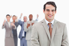 Smiling salesman with cheering team behind him Royalty Free Stock Image