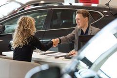 Smiling salesman doing handshake with female customer Stock Photo