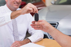 Smiling salesman giving a customer car keys Royalty Free Stock Image