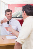 Smiling salesman giving a customer car keys Royalty Free Stock Photo