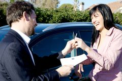 Smiling salesman giving documents and keys of new car to woman Royalty Free Stock Photography