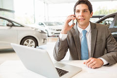 Smiling salesman having a phone call. At new car showroom stock photography