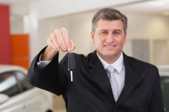 Smiling salesman holding a customer car key Royalty Free Stock Photos