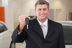Smiling salesman holding a customer car key Stock Images