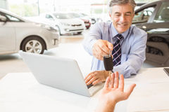 Smiling salesman holding a customer car key Stock Photos