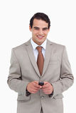 Smiling salesman holding his cellphone Stock Photo