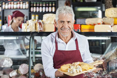 Smiling Salesman Holding Various Cheese On Board In Store. Portrait of smiling salesman holding various cheese on cutting board with colleague in background at Stock Photo