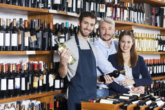 Smiling Salesman Holding Wine Bottles While Couple Standing In S. Portrait of smiling salesman holding wine bottles while couple standing in shop stock image