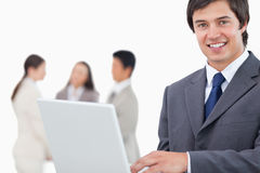 Smiling salesman with laptop and colleagues behind him Stock Image