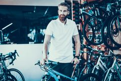 Smiling Salesman Poses near Bicycle in Sport Shop. Portrait of Cheerful Bearded Caucasian Male Seller Wearing White T-Shirt Looking at Camera. Happy Consultant royalty free stock photos