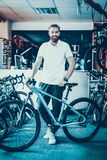 Smiling Salesman Poses near Bicycle in Sport Shop. Portrait of Cheerful Bearded Caucasian Male Seller Wearing White T-Shirt Looking at Camera. Happy Consultant stock photography