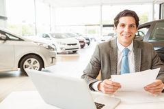 Smiling salesman reading a document Royalty Free Stock Image