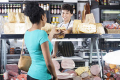 Smiling Salesman Selling Cheese To Female Customer. Smiling young salesman selling cheese to female customer at grocery shop Stock Image