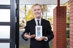 Smiling salesman selling perfume Royalty Free Stock Image