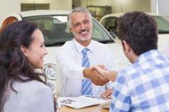 Smiling salesman shaking a customer hand Royalty Free Stock Image