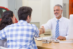 Smiling salesman shaking a customer hand Royalty Free Stock Images