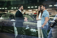 Smiling salesman showing new car to a couple in showroom. Salon Royalty Free Stock Photo