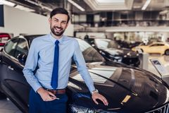 Smiling salesman in dealership salon. Smiling salesman standing at the car with smartphone in dealership salon and looking at the camera royalty free stock photography