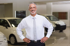 Smiling salesman standing with hands on hips Royalty Free Stock Image