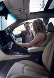 Smiling salesman talking to female customer sitting in car stock photo