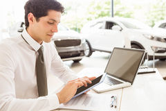 Smiling salesman using tablet at his desk Royalty Free Stock Image