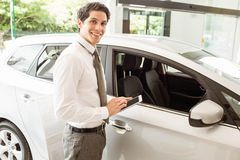 Smiling salesman using tablet near a car Stock Images