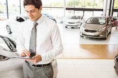 Smiling salesman using tablet near a car. At new car showroom Stock Photos