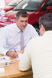Smiling salesman writing on contract Royalty Free Stock Image