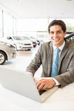 Smiling salesman writing on his laptop Stock Images