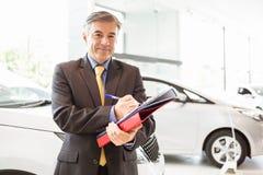 Smiling salesman writing on workbooks Royalty Free Stock Image