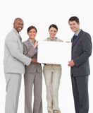 Smiling salesteam holding blank sign together Royalty Free Stock Image